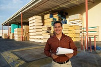 Man with clipboard outside warehouse full of wood (thumbnail)