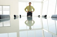 Businessman with hands on hips at conference table portrait (thumbnail)