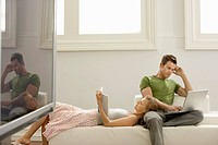 Couple relaxing together on sofa man using laptop woman reading