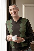 Smiling man with cup of coffee portrait