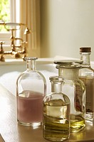 Bottles of Bath Oils on edge of bathtub filled with bubbles