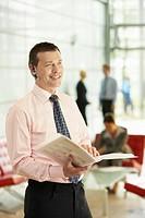 Businessman Holding Report and Using Wireless Headset (thumbnail)