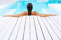 Young Woman in Swimming Pool resting on poolside back view