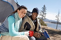 Young Couple sitting at campsite drinking from thermos (thumbnail)