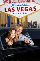 Couple sitting in limousine with drinking glasses in front of Welcome to Las Vegas sign (thumbnail)