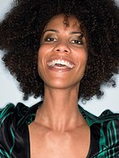 Woman with afro smiling head and shoulders in studio