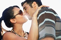 Young couple kissing portrait side view