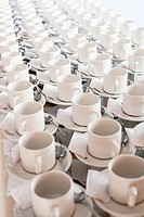 Rows of stacked teacups and saucers elevated view