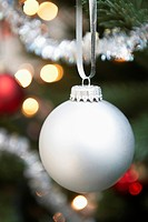Silver bauble hanging from christmas tree close up