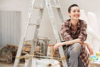 Female interior decorator sitting on ladder in work site front view (thumbnail)