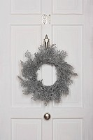 Christmas wreath hanging on white door (thumbnail)