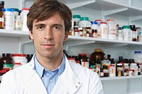 Male lab worker standing pill bottles behind
