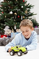 Little Boy Playing with Toy Truck by christmas tree (thumbnail)