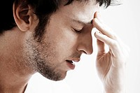 Man with Headache touching forehead close up