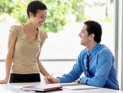 Smiling businessman and businesswoman at office table talking