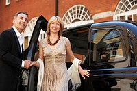 Well dressed couple exiting London taxi