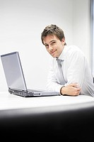 Contented Businessman sitting at desk with Laptop portrait
