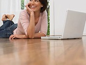 Woman laying on floor using laptop