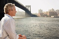 Man looking at river by Brooklyn Bridge