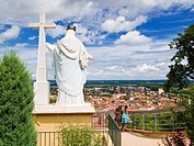 Statue of the Madonna and cross overlooking the rooftops of historic Moissac, Tarn et Garonne, France, Europe