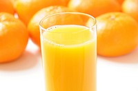 Glass of orange juice amongst oranges