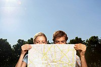 Vacationing couple in park looking at large map