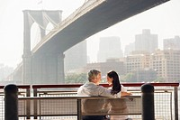 Couple relaxing on bench under Brooklyn Bridge