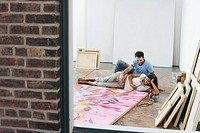 Couple reclining by painting on floor of studio view through window (thumbnail)