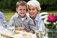 Grandmother with grandson 7-9 on lap sitting at table in garden (thumbnail)