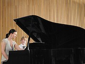 Teacher with student sitting at piano in music class (thumbnail)