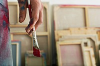 Artist holding paint brush standing in studio close up on hand