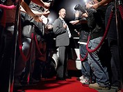 Man on red carpet in front of paparazzi