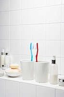 Toothbrushes face to face on shelf in white bathroom