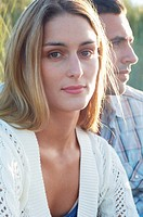 Young Woman Sitting by Boyfriend in tall grass portrait