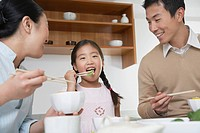 Young couple and daughter eating a meal with chopsticks (thumbnail)