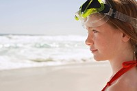 Girl 7_9 in swimming goggles on beach close_up