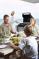 Family sitting around table outside eating Barbecue mother standing at grill grilling