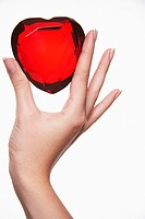 Woman holding up heart_shaped jewel between finger and thumb close_up of hand