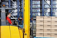 Warehouse Worker Operating Forklift side view