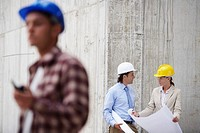 Managers and worker on construction site