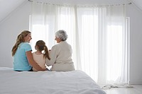 Grandmother mother and daughter sitting on bed in bedroom