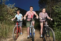 Teenage boys and girl 16_17 years riding bikes on country road in evening