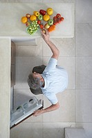 Mature man squatting putting fruit in refrigerator view from above