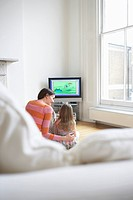 Mother and daughter 5_6 watching cartoons in television back view
