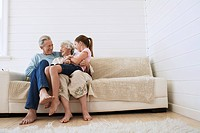 Senior man and woman sitting with granddaughter on woman's knee on couch
