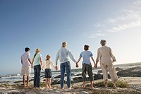 Three generation family holding hands on seashore back view (thumbnail)