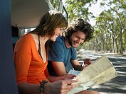 Young couple looking at map sitting in open camper van at side of road