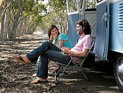 Couple sitting in deck chairs beside camper van parked at side of road