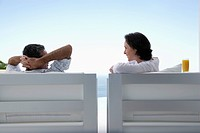 Couple talking sitting on lounge chairs outdoors