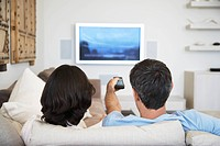 Couple using remote control sitting in front of television in living room back view (thumbnail)